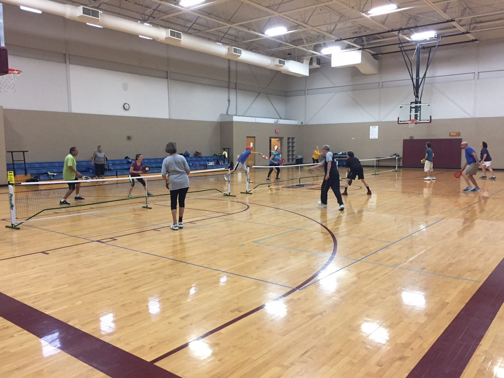6 men and 6 women playing 3 games of doubles Pickleball on 3 Pickleball courts set up in a gym.