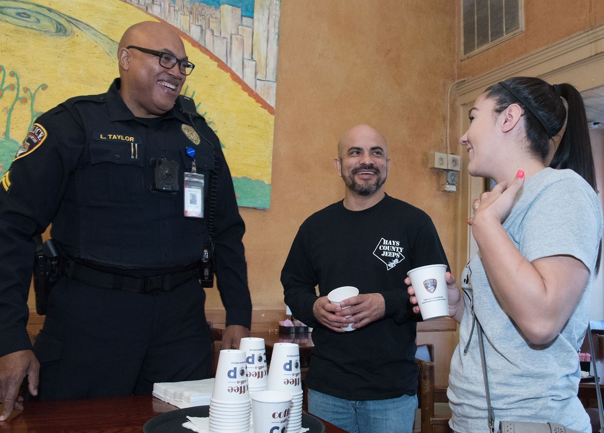 Photo of police officer speaking with community member while all are drinking coffee in a restaurant