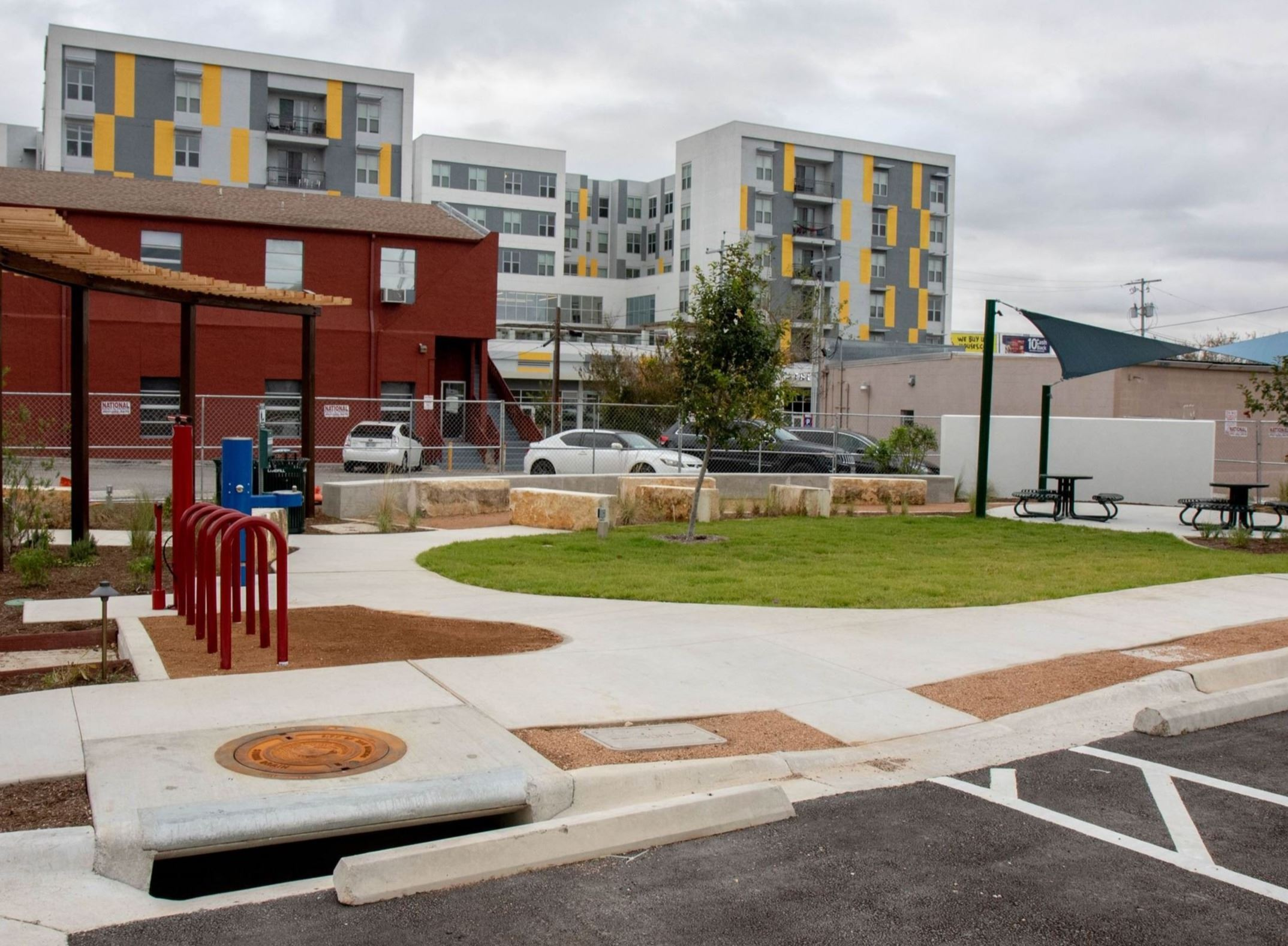 Photo from alley/street angle of Mobility Hub, featuring parking spots, a grassy area, picnic tables