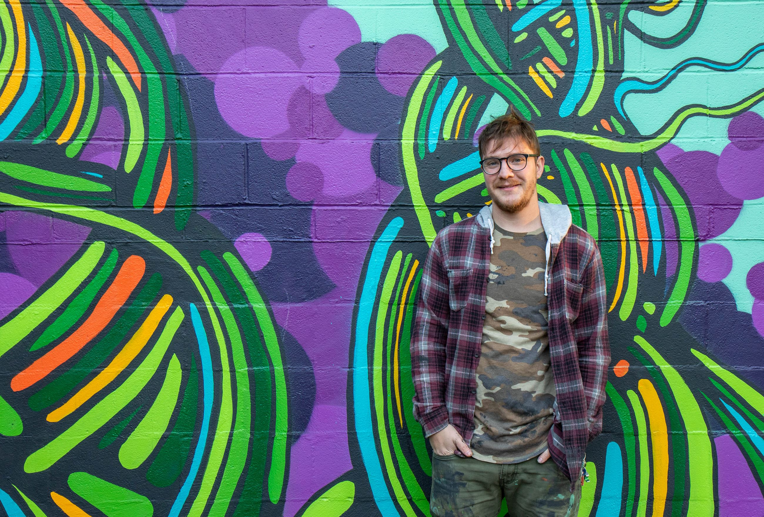 A man wearing glasses, a camo shirt and plaid jacket stands in front of a brightly colored mural of