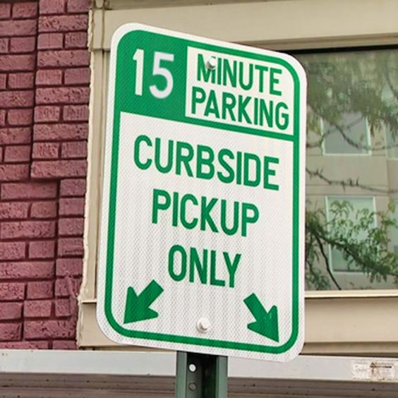 A green and white curbside parking sign